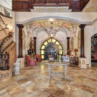 Ispirazione per un ampio ingresso mediterraneo con pareti beige, pavimento in travertino, una porta a due ante, una porta in legno scuro e pavimento giallo