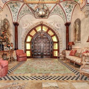 На фото: огромное фойе в средиземноморском стиле с бежевыми стенами, полом из травертина, двустворчатой входной дверью, входной дверью из темного дерева и желтым полом с