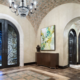 Tuscan entryway photo in Houston with beige walls and a glass front door