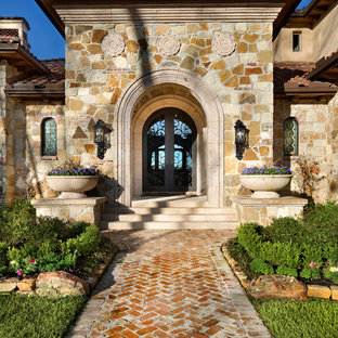 Tuscan entryway photo in Houston with a glass front door