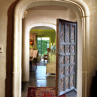 Inspiration for a large mediterranean concrete floor entryway remodel in Austin with beige walls and a dark wood front door