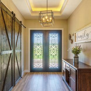 オースティンの中くらいの両開きドアラスティックスタイルのおしゃれな玄関ロビー (ベージュの壁、淡色無垢フローリング、黒いドア、茶色い床、折り上げ天井) の写真