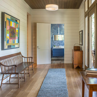 Inspiration for a large transitional medium tone wood floor and brown floor entryway remodel in Other with white walls and a glass front door