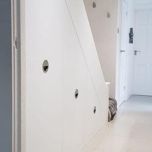 Exempel på ett mellanstort modernt kapprum, med vita väggar, klinkergolv i keramik, en enkeldörr, en vit dörr och vitt golv