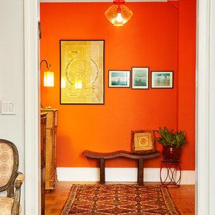 На фото: маленькое фойе в стиле фьюжн с оранжевыми стенами, светлым паркетным полом, одностворчатой входной дверью и белой входной дверью с