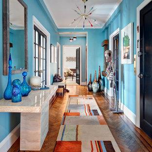 Foto de hall contemporáneo con paredes azules, suelo de madera en tonos medios, puerta simple, puerta negra y suelo naranja