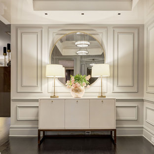 Large trendy dark wood floor and black floor foyer photo in New York with white walls