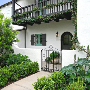 Example of a tuscan entryway design in San Diego with white walls and a black front door