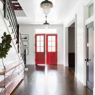 ニューヨークの大きい両開きドアカントリー風おしゃれな玄関ロビー (白い壁、濃色無垢フローリング、赤いドア、茶色い床) の写真