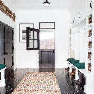 Inredning av ett lantligt stort kapprum, med en tvådelad stalldörr, vita väggar, kalkstensgolv, en svart dörr och svart golv