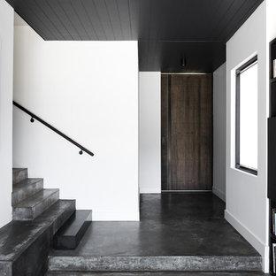 Inspiration för en funkis hall, med vita väggar, betonggolv, en enkeldörr, mörk trädörr och grått golv