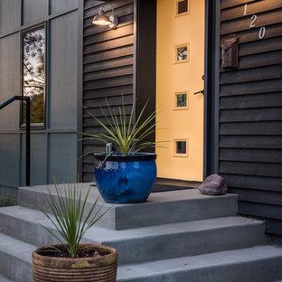 Immagine di una piccola porta d'ingresso minimal con pareti nere, pavimento in cemento, una porta singola e una porta gialla