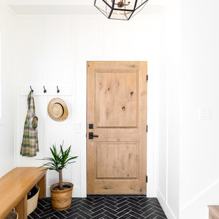 Стильный дизайн: тамбур среднего размера в стиле кантри с полом из сланца, одностворчатой входной дверью, входной дверью из светлого дерева, черным полом и белыми стенами - последний тренд