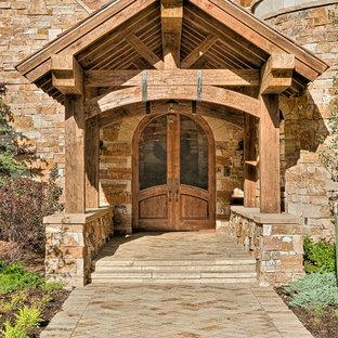 Diseño de puerta principal rústica, grande, con puerta doble, paredes marrones, suelo de piedra caliza y puerta de vidrio