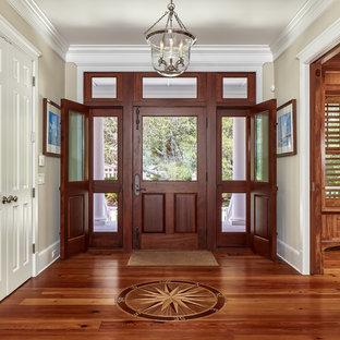 Idée de décoration pour un hall d'entrée marin avec un mur beige, un sol en bois brun et une porte en bois foncé.