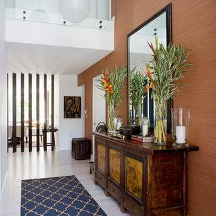 Imagen de hall contemporáneo con parades naranjas, suelo de madera clara y suelo blanco