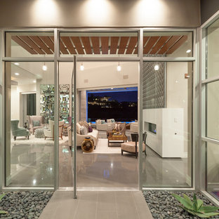 Entryway - large contemporary ceramic tile entryway idea in Las Vegas with beige walls and a glass front door