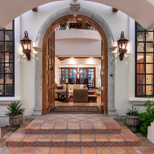 Idee per una porta d'ingresso mediterranea di medie dimensioni con pareti bianche, pavimento in terracotta e una porta a due ante