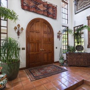 Esempio di un ingresso mediterraneo di medie dimensioni con pareti bianche, pavimento in terracotta, una porta a due ante e una porta in legno scuro