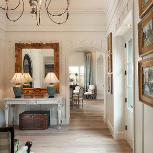 Idéer för att renovera en vintage foajé, med vita väggar, ljust trägolv och glasdörr