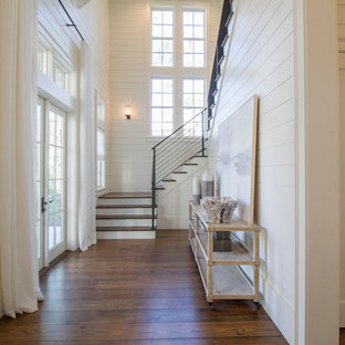 Ejemplo de puerta principal costera con paredes blancas, suelo de madera oscura, puerta doble y puerta blanca