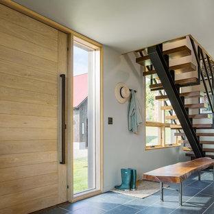 Cette image montre un hall d'entrée minimaliste de taille moyenne avec un mur gris, un sol en carrelage de porcelaine, une porte pivot, une porte en bois clair et un sol gris.