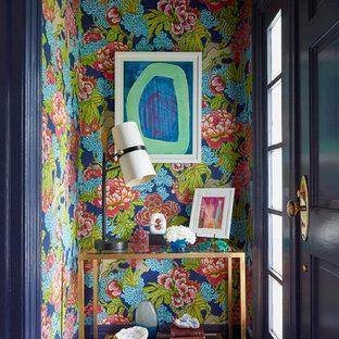 Cette image montre une petit entrée traditionnelle avec un mur multicolore, une porte simple, une porte bleue, un sol bleu et un couloir.