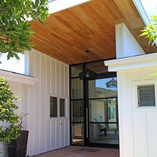 Свежая идея для дизайна: входная дверь среднего размера в стиле кантри с белыми стенами, паркетным полом среднего тона, поворотной входной дверью, металлической входной дверью, коричневым полом, деревянным потолком и панелями на части стены - отличное фото интерьера