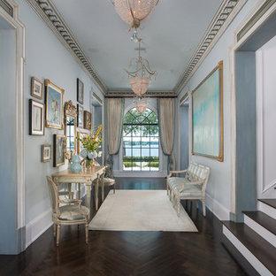 Cette image montre un grand hall d'entrée style shabby chic avec un mur bleu et un sol en bois foncé.