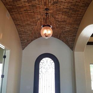 Inredning av en klassisk stor ingång och ytterdörr, med gula väggar, marmorgolv, en enkeldörr och metalldörr