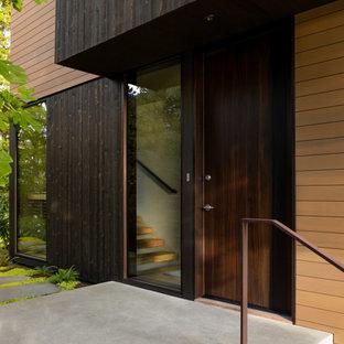 シアトルの片開きドアコンテンポラリースタイルのおしゃれな玄関 (無垢フローリング、濃色木目調のドア、板張り壁) の写真