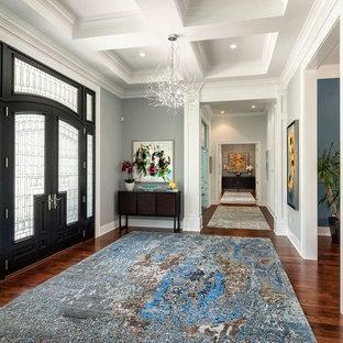 Diseño de distribuidor clásico renovado, grande, con paredes azules, suelo de madera en tonos medios, puerta doble y puerta negra