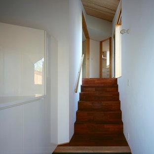 Diseño de hall minimalista, de tamaño medio, con paredes blancas, suelo de cemento, puerta simple, puerta de madera clara y suelo negro