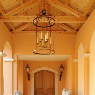 ニースの巨大な両開きドア地中海スタイルのおしゃれな玄関ドア (ピンクの壁、ライムストーンの床、淡色木目調のドア、ベージュの床) の写真