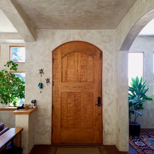 Example of a small tuscan brown floor and concrete floor entryway design in Other with beige walls and a medium wood front door