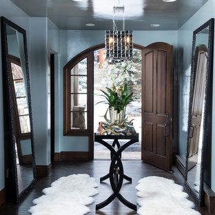 デンバーの小さい片開きドアコンテンポラリースタイルのおしゃれな玄関ロビー (青い壁、濃色無垢フローリング、濃色木目調のドア、茶色い床) の写真