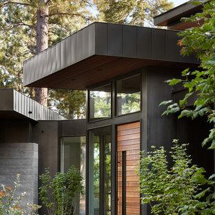 Modelo de puerta principal contemporánea, extra grande, con suelo de cemento, puerta simple, puerta de madera en tonos medios, suelo gris y paredes negras