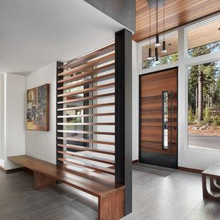 Imagen de puerta principal actual, extra grande, con suelo de baldosas de porcelana, puerta simple, puerta de madera en tonos medios, suelo gris y paredes blancas