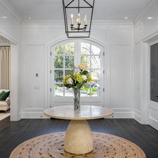 ロサンゼルスの両開きドアトランジショナルスタイルのおしゃれな玄関ドア (白い壁、濃色無垢フローリング、白いドア、茶色い床、パネル壁) の写真