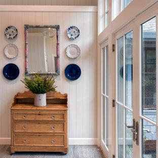 Réalisation d'un petit vestibule craftsman avec un mur blanc, sol en stratifié, une porte double, une porte blanche et un sol gris.