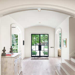 Entryway - large country light wood floor and beige floor entryway idea in Houston with a glass front door and white walls