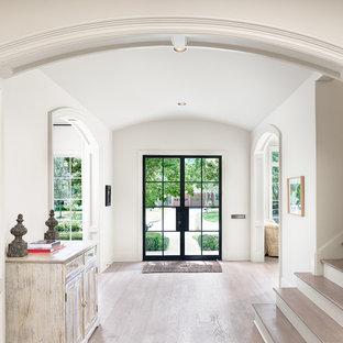 Foto de distribuidor de estilo de casa de campo, grande, con puerta doble, puerta de vidrio, paredes blancas, suelo de madera clara y suelo beige
