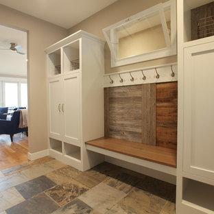 Modelo de puerta principal marinera, pequeña, con paredes beige, suelo de pizarra, puerta simple y puerta de madera oscura