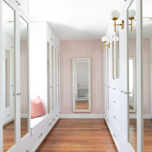 Photo of a large beach style entryway in Gold Coast - Tweed with pink walls, medium hardwood floors and brown floor.