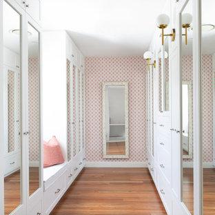 Cette image montre une grand entrée marine avec un mur rose, un sol en bois brun et un sol marron.