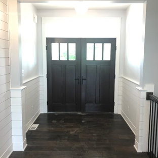 Example of a mid-sized transitional dark wood floor and brown floor entryway design in Other with white walls and a dark wood front door