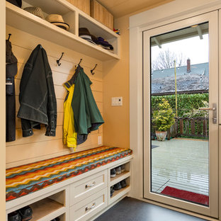 Exemple d'une petit entrée craftsman avec un vestiaire, un mur jaune, un sol en linoléum, une porte simple, une porte en verre et un sol gris.