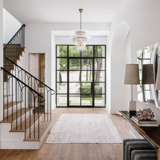 Example of a large tuscan light wood floor and beige floor entryway design in Austin with white walls and a black front door