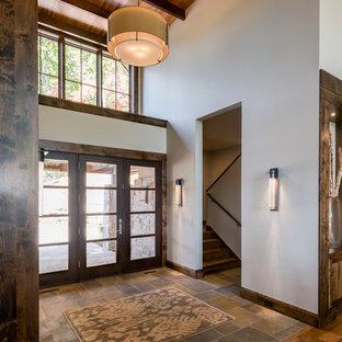 Cette image montre une grande porte d'entrée chalet avec un mur beige, un sol en ardoise, une porte simple et une porte en verre.