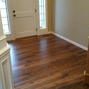 Mid-sized arts and crafts medium tone wood floor entryway photo in Boise with yellow walls and a white front door